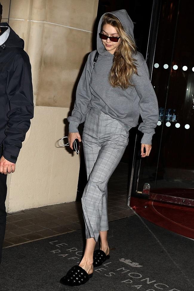 Gigi diện cả cây xám thanh lịch với áo hoodie, quần kẻ caro và dép mules cá tính.