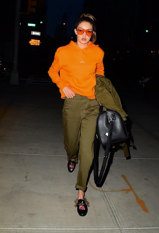 Gigi chọn áo hoodie cam tạo điểm nhấn cho set đồ nâu ghi tối màu.