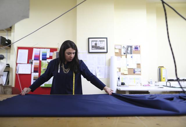 Trong ảnh, một nhân viên đang trải một phần vải lấy tại kho để chuẩn bị cho việc cắt mẫu.